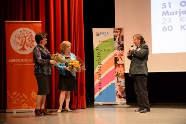 Liittokokouksen puheenjohtaja Mauri Tammela onnittelee liiton 1. varapuheenjohtajaksi valittua Kuopion kansalaisopiston rehtori Kirsti Turusta (Kuopion kansalaisopisto) ja 2. varapuheenjohtajaksi valittua Oulu-opiston rehtori Outi Lohea.